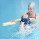 Little boy swimming on back with water noodle in swimming pool. — Stock Photo
