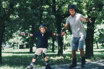 Grandfather and grandson enjoying rollerskating in summer park. — Stock Photo