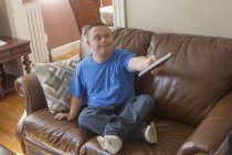 Подросток с синдромом Дауна сидит на диване с пультом от телевизора . — стоковое фото
