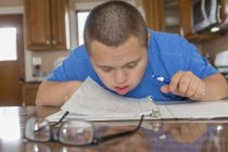 Teenage boy with Down Syndrome studying at home. — Stock Photo