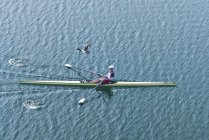 Male athlete rowing single scull rowing boat. — Stock Photo