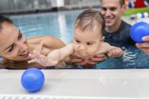 Instructor with baby boy and mother playing in pool. — Stock Photo