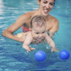 Cute baby boy swimming with mother in pool and trying catching ball. — Stock Photo