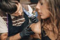Татуювальник зосереджена на тату роботи на жіночому клієнті. — стокове фото
