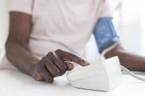 Mujer madura prueba de presión arterial con la máquina . - foto de stock