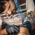 Maestro tatuando la piel femenina en detalle en el estudio . - foto de stock