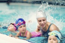 Swimming instructor with children in swimming pool. — Stock Photo