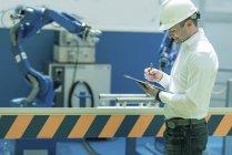 Ingeniero que trabaja en fábrica, tiene lista de verificación y supervisa . - foto de stock
