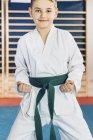 Junge mit grünem Gürtel posiert im Taekwondo-Kurs. — Stockfoto