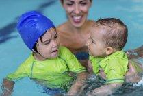 Lindos niños pequeños con madre en la piscina . - foto de stock