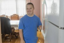 Teenage boy with Down Syndrome opening refrigerator. — Stock Photo
