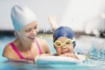 Boy with board splashing in swimming class with instructor in public pool. — Stock Photo