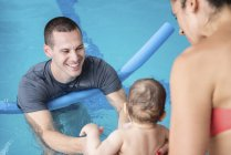 Instructor with water noodle with baby boy and mother playing in pool. — Stock Photo