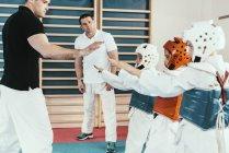 Taekwondo instructors working with children in class. — Stock Photo