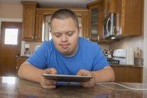 Adolescent garçon avec trisomie 21 en utilisant tablette . — Photo de stock