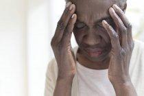Mulher madura tocando a cabeça na dor com as mãos . — Fotografia de Stock