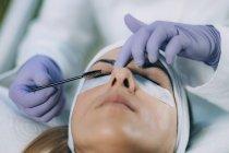 Косметолог для завивки вій у пацієнта і використання бігуді в процедурі підйому вій. — стокове фото