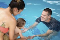 Baby entering swimming pool water for first time. — Stock Photo