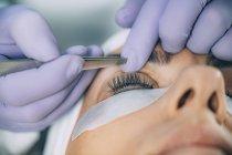 Cosmetologo che esegue sollevamento ciglia su paziente femminile in salone . — Foto stock