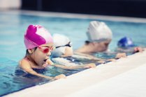 Children with swimming instructor making bubbles by pool edge. — Stock Photo