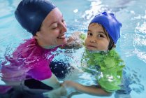 Little boy learning swimming with female instructor in pool. — Stock Photo