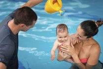 Instructor with baby boy and mother playing in pool and spraying baby with watering can. — Stock Photo