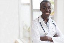 Reife Ärztin lächelnd mit gekreuzten Armen. — Stockfoto