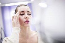 Femme regardant le visage dans le miroir dans la clinique cosmétique . — Photo de stock