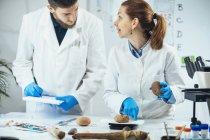 Archéologues mesurant des artefacts anciens à l'échelle numérique en laboratoire . — Photo de stock