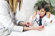 Niño pequeño usando estetoscopio como jugar a ser médico en el consultorio de pediatría . - foto de stock