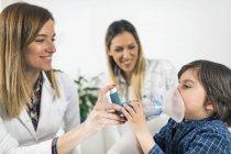 Pulmonologo aiutare bambino con inalatore, madre in background. — Foto stock