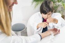 Niño jugando a ser médico en la oficina de pediatría femenina . - foto de stock