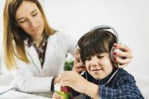 Женщина-врач надевает наушники на мальчика, который проходит тест на слух . — стоковое фото