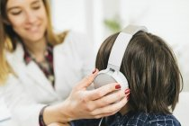 Female doctor putting headphones on boy having hearing test. — Stock Photo