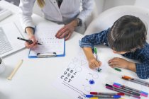 Хлопчик фарбування форми з барвистими ручками для тестування психології розвитку в жіночому лікарському кабінеті. — стокове фото