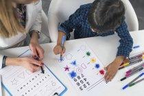 Маленький хлопчик фарбує форми з барвистими ручками для тестування психології розвитку в психологічному офісі. — стокове фото