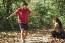 Young man exercising with elastic resistance bands with personal trainer in park. — Stock Photo