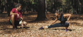 Young woman stretching legs after training with personal trainer in park. — Stock Photo
