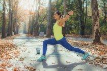 Donna che si allunga con le braccia tese nel parco autunnale . — Foto stock