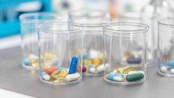 Variedad de píldoras farmacológicas en vasos de plástico desechables, concepto de medicación . - foto de stock