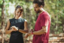 Молодая пара проверяет успехи на умных часах во время тренировок на открытом воздухе . — стоковое фото