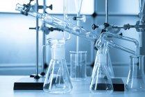 Appareils de chimie verrerie sur table en laboratoire . — Photo de stock