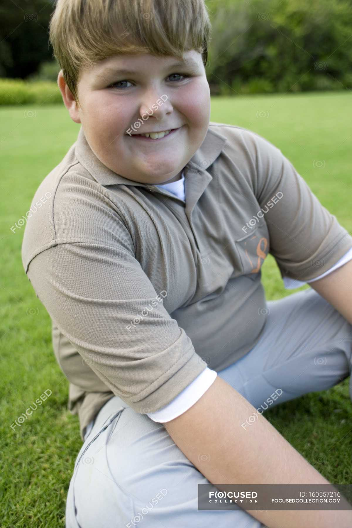 Happy chubby boy sitting on grass. — kid, happiness