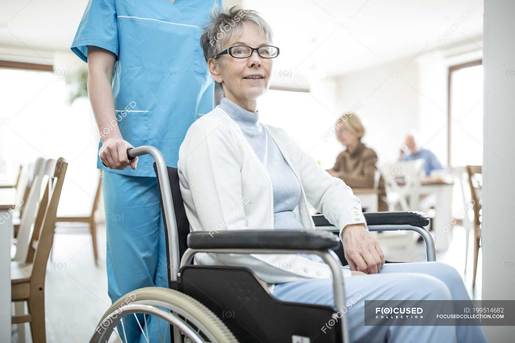 Nurse Pushing Senior Woman In Wheelchair In Care Home Senior Man Casual Clothing Stock Photo 199514682
