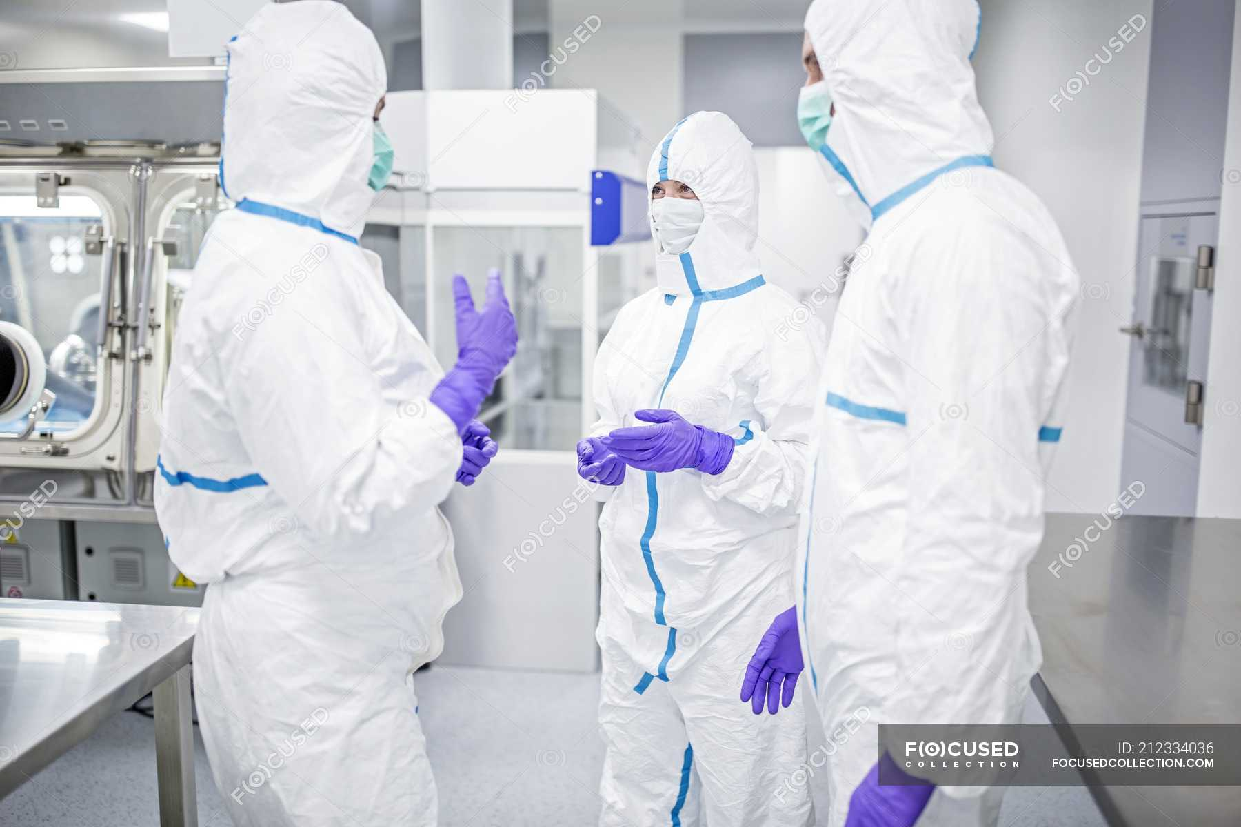 Lab technicians in protective suits and masks discussing in sterile