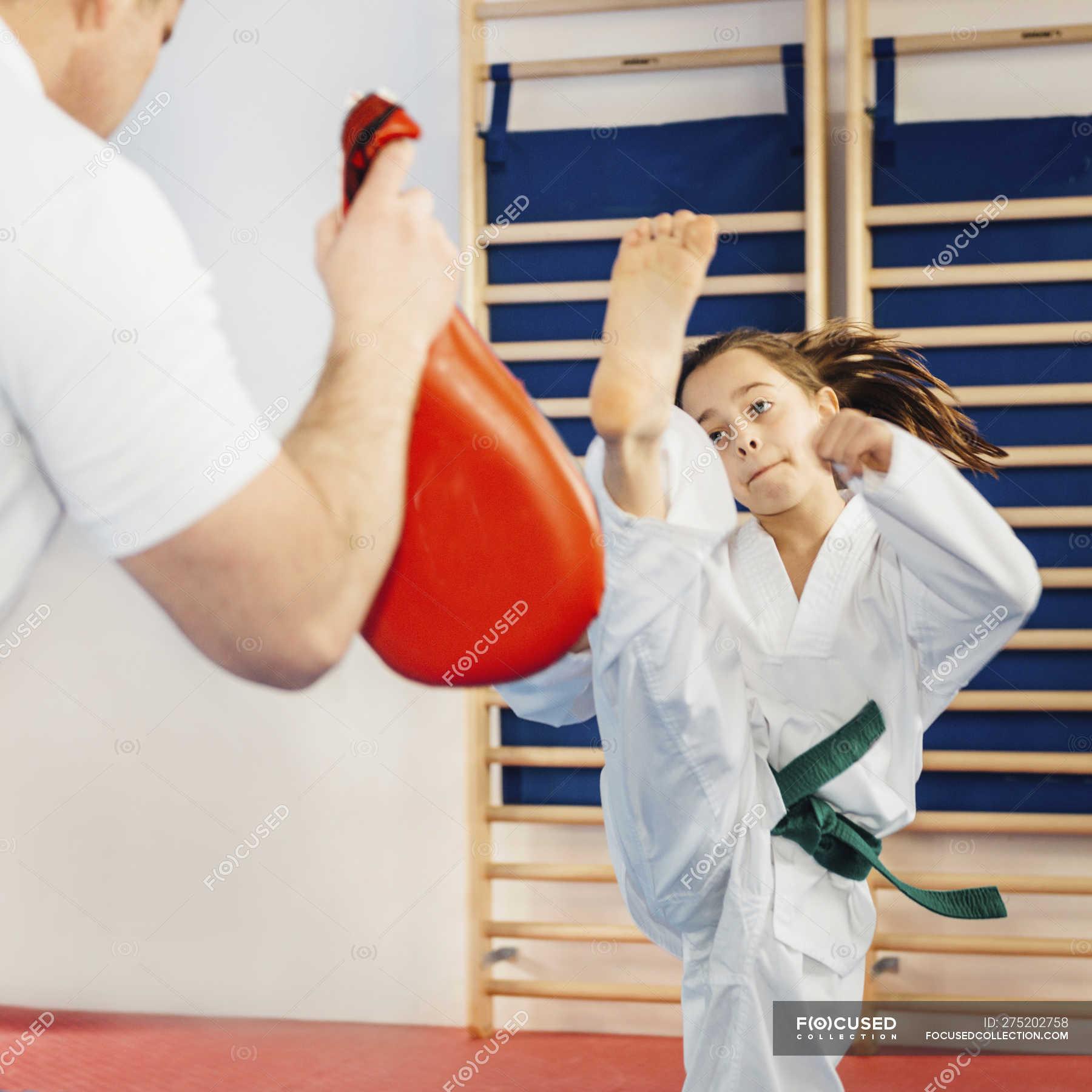 Girl kicking punch bag in taekwondo class with trainer