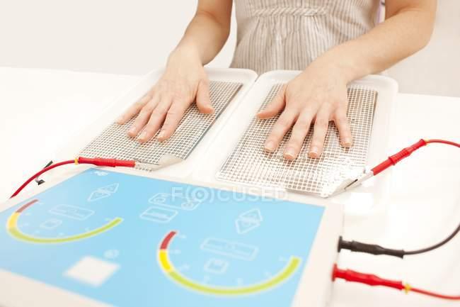 Frau unterzieht sich einer Iontophorese-Behandlung bei übermäßigem Schwitzen der Handflächen. — Stockfoto
