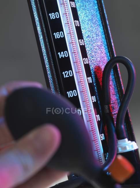Nahaufnahme der Hand einer Person, die die Glühbirne des Blutdruckmessgeräts drückt. — Stockfoto