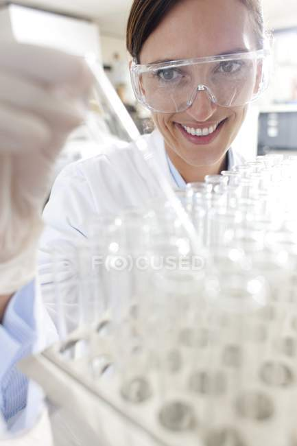 Female scientist taking testing tube from tray for scientific research. — Stock Photo