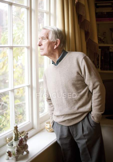 Lonely senior man looking through window in home interior. — Stock Photo